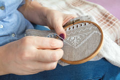 Woman hands doing openwork embroidery on homespun linen. Royalty Free Stock Images