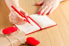 Woman hands drawing or writing, gift box, red hearts on wooden t Stock Photography