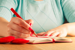 Woman hands drawing or writing, gift box, red hearts on wooden t Royalty Free Stock Image