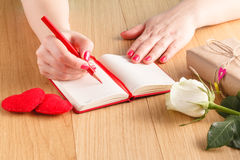 Woman hands drawing or writing, gift box, red hearts on wooden t Royalty Free Stock Images
