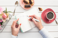 Woman hands drawing or writing with ink pen in open notebook on white wooden table. Bird eye view Royalty Free Stock Images