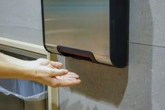 Woman hands dries wet hand in modern vertical hand dryer in public restroom. WC stock image