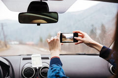 Woman hands driving and taking photos with mobile phone royalty free stock photos