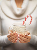 Woman hands with elegant french manicure nails design holding a cozy knitted mug with cocoa and a candy cane. Stock Images