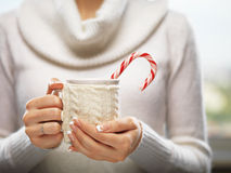 Woman hands with elegant french manicure nails design holding a cozy knitted mug with cocoa and a candy cane. Stock Photos
