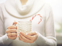 Woman hands with elegant french manicure nails design holding a cozy knitted mug with cocoa and a candy cane. Stock Photo