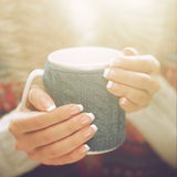 Woman hands with elegant french manicure nails design holding a cozy knitted mug. Stock Images
