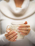 Woman hands with elegant french manicure nails design holding a cozy knitted mug. Winter and Christmas concept. Stock Image