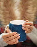 Woman hands with elegant french manicure nails design holding a cozy knitted mug. Winter and Christmas time concept. Royalty Free Stock Photos