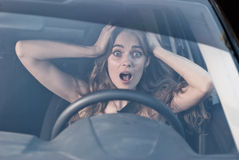 Woman with hands on eyes sitting scared in car Stock Photo