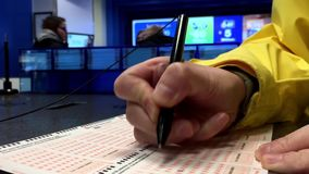Woman hands filling lucky number on daily grand lottery ticket stock footage