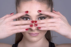 Woman with hands and fingers over face Royalty Free Stock Images