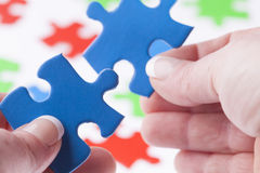 Woman hands fitting jigsaw puzzle pieces together Royalty Free Stock Image