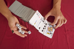 Woman hands flipping playing cards holding dice Royalty Free Stock Image