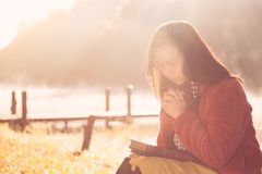 Woman hands folded in prayer on a Holy Bible for faith. In beautiful nature background with sunlight in vintage color tone royalty free stock photography