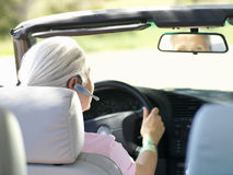 Woman with hands-free device in car, rear view Stock Photo