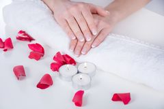 Woman hands with french manicure modern style on towel with red rose petals and candle in beauty salon royalty free stock photo