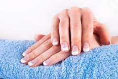 Woman hands with french manicure nails on blue towel. Femininity and Beauty concept image. Close up Stock Photos