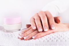 Woman hands with french manicure and pink hand cream on white towel. Femininity and Beauty concept image. Close up Royalty Free Stock Photography