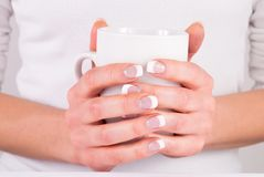 Woman hands with french nails manicure holding cup of coffee. Coffee cup in young woman hands with french nails manicure. Close up. Beauty and Drink concept Royalty Free Stock Photo