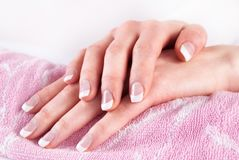 Woman hands with french nails on pink towel. Femininity and Beauty concept image. Close up Stock Images