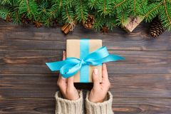 Woman hands give wrapped christmas handmade present in paper with blue ribbon. Present box on holiday on dark wooden table, top vi. Ew stock images