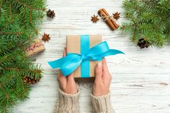 Woman hands give wrapped christmas handmade present in paper with blue ribbon. Present box on holiday on white wooden table, top v. Iew stock photo