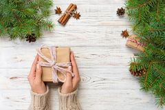 Woman hands give wrapped christmas handmade present in paper with pink ribbon. Present box on holiday on white wooden table, top v. Iew royalty free stock photos