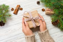 Woman hands give wrapped christmas handmade present in paper with pink ribbon. Present box on holiday on white wooden table, top v. Iew stock image