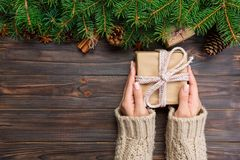 Woman hands give wrapped christmas handmade present in paper with pink ribbon. Present box on holiday on dark wooden table, top vi. Ew royalty free stock photos