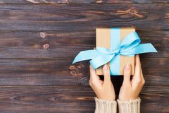 Woman hands give wrapped valentine or other holiday handmade present in paper with blue ribbon. Present box, decoration of gift on Royalty Free Stock Images