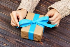 Woman hands give wrapped valentine or other holiday handmade present in paper with blue ribbon. Present box, decoration of gift on Royalty Free Stock Photography