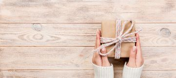 Woman hands give wrapped valentine or other holiday handmade present in paper with blue ribbon. Present box, decoration of gift on. White wooden table, Top view stock images