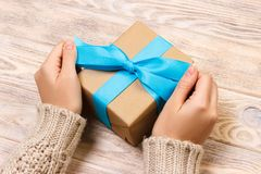 Woman hands give wrapped valentine or other holiday handmade present in paper with blue ribbon. Present box, decoration of gift on Royalty Free Stock Photos