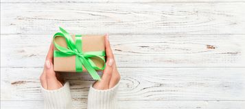 Woman hands give wrapped valentine or other holiday handmade present in paper with green ribbon. Present box, decoration of gift. On wooden table, Top view stock photo