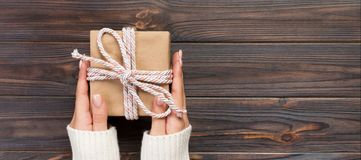 Woman hands give wrapped valentine or other holiday handmade present in paper with pink ribbon. Present box, decoration of gift on. Black wooden table, Top view royalty free stock photography