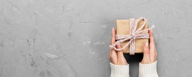 Woman hands give wrapped valentine or other holiday handmade present in paper with red ribbon. Present box, decoration of gift on. White cement table, Top view royalty free stock image