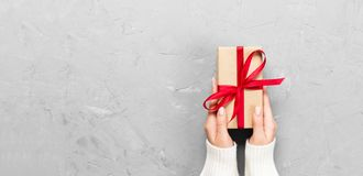 Woman hands give wrapped valentine or other holiday handmade present in paper with red ribbon. Present box, decoration of gift on. White cement table, Top view stock photo