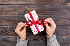 Woman hands give wrapped valentine or other holiday handmade present in paper with red ribbon. Present box, red heart decoration. Of gift on wooden table, top stock photography