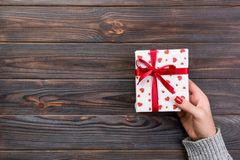 Woman hands give wrapped valentine or other holiday handmade present in paper with red ribbon. Present box, red heart decoration. Of gift on wooden table, top royalty free stock photo