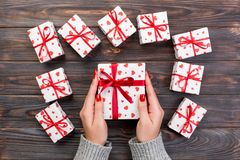 Woman hands give wrapped valentine or other holiday handmade present in paper with red ribbon. Present box, red heart decoration. Of gift on wooden table, top royalty free stock photography