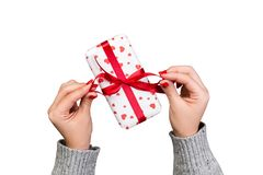 Woman hands give wrapped valentine or other holiday handmade present in paper with red ribbon. Present box, red heart decoration. Of gift on white background stock photography