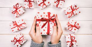 Woman hands give wrapped valentine or other holiday handmade present in paper with red ribbon. Present box, red heart decoration. Of gift on wooden table, top stock photo