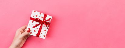 Woman hands give wrapped valentine or other holiday handmade present in paper with red ribbon. Present box, red heart decoration. Of gift on pink table, Top royalty free stock photo