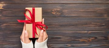 Woman hands give wrapped valentine or other holiday handmade present in paper with red ribbon. Present box, decoration of gift on. Black wooden table, Top view stock image