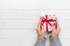 Woman hands give wrapped valentine or other holiday handmade present in paper with red ribbon. Present box, red heart decoration. Of gift on wooden table, top stock image
