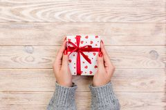 Woman hands give wrapped valentine or other holiday handmade present in paper with red ribbon. Present box, red heart decoration. Of gift on wooden table, top stock images
