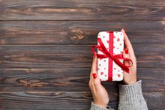 Woman hands give wrapped valentine or other holiday handmade present in paper with red ribbon. Present box, red heart decoration. Of gift on wooden table, top stock photos