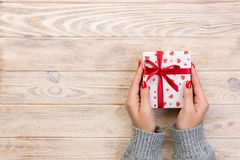 Woman hands give wrapped valentine or other holiday handmade present in paper with red ribbon. Present box, red heart decoration. Of gift on wooden table, top royalty free stock photos