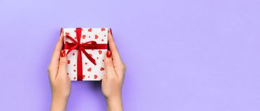 Woman hands give wrapped valentine or other holiday handmade present in paper with red ribbon. Present box, red heart decoration. Of gift on purple table, Top stock images